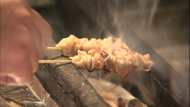 A chef turns yakitori chicken skewers above a charcoal grill.