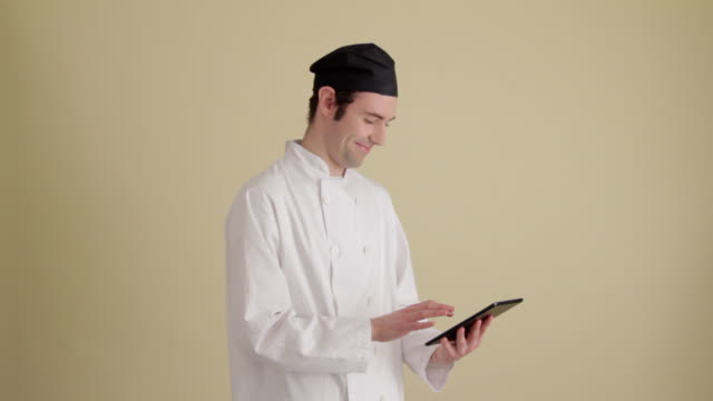 MWS Chef using mini tablet profile  Looking up at camera and smiling