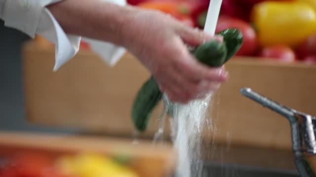 Chef washing fresh cucumber
