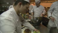 Chefs dish food onto plates in a restaurant.