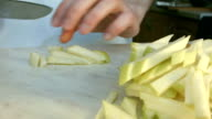 Chefs hands cutting a green fresh apple.