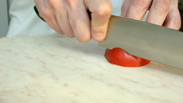 Chefs hands cutting a red fresh tomato.