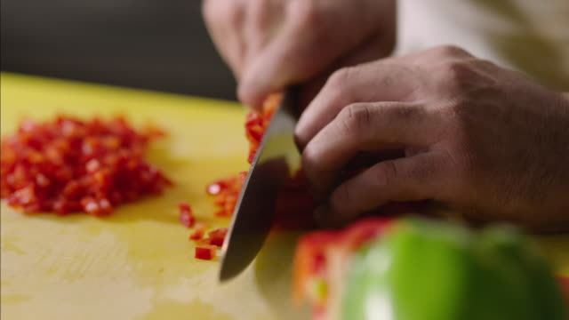 Chef's hands finely dice red pepper in restaurant kitchen