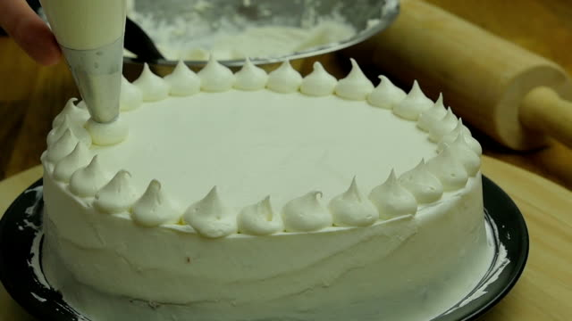 chef's piping cream  on cake slow motion
