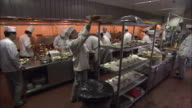 Chefs prepare and present food in a restaurant kitchen.