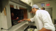 Chefs preparing food in busy kitchen