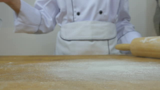 chef's sprinkling flour slow motion