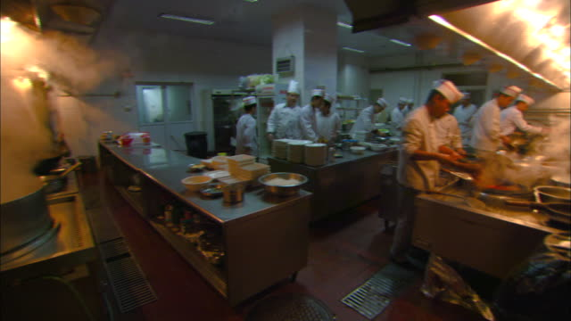 Chefs work in the kitchen of a Chinese restaurant.