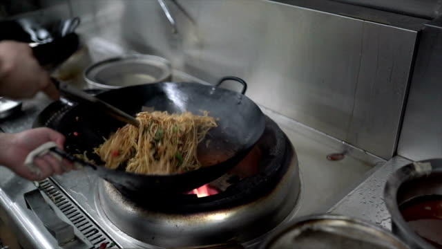 cheif cooking chinese rice noodle in the kitchen