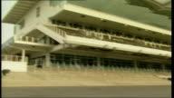 Cheltenham Racecourse general views ENGLAND Gloucestershire Cheltenham Racecourse EXT Empty stands / PAN along empty stands to racecourse / deserted...