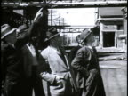 Chemical factory building damaged by Japanese VS FAO representatives dressed in suits hats looking at building pointing talking VS Building back side