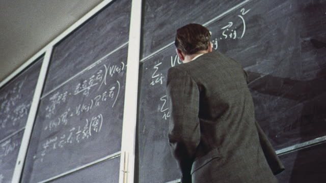 1965 MONTAGE Chemistry instructor writing on blackboard during a lecture and talking to two students / Brighton, England, United Kingdom