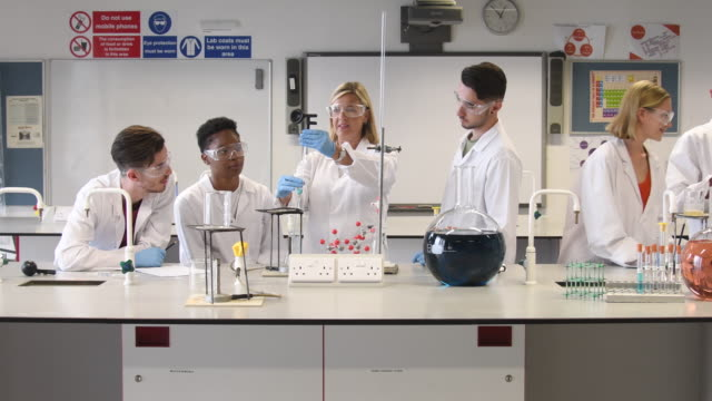 Chemistry student in laboratory with teacher doing experiment