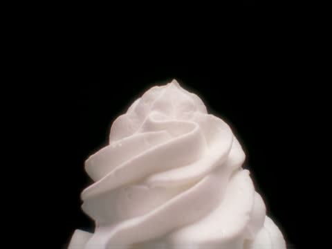 A cherry being placed on a mound of whipped cream