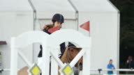 SLO MO DS Chestnut horse jumping obstacle with rider