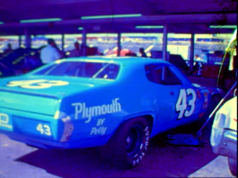 Chevrolet Monte Carlo stock car stopping for pit stop pit crew hustling to work at Charlotte Motor Speedway / 1971 Plymouth Road Runner stock car...