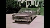 Chic, stylish woman drives 1966 AMC Rambler Classic convertible