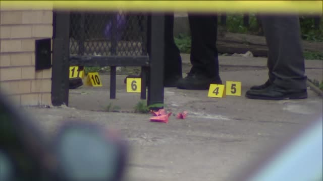 WGN Chicago Police At A Crime Scene with evidence markers and yellow police tape in the South Austin neighborhood on June 6 2015
