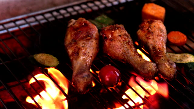 Chicken drumsticks being cooked on flaming barbecue