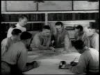 Chief of Naval Operations sign Men in suits in office looking at world wall map US Officers looking at map on table GUAM Vehicle driving onto Navy...
