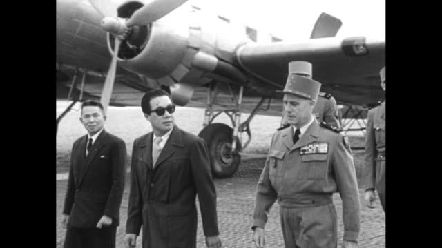 VS chief of state of the State of Vietnam Bao Dai former emperor deplanes on small airfield greets French generals he wears sunglasses / Bao Dai...
