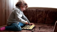 Child arranging black chess pieces on the board