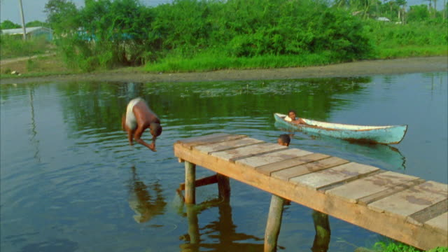 A child does a back flip into a river as a friend watches from a canoe. Available in HD.