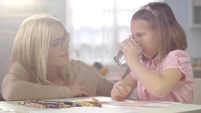 Kind huiswerk thuis. Moeder brengt een glas zelfs