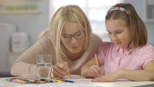 Child Doing Homework at Home. Mother Brings a Glass of Wather