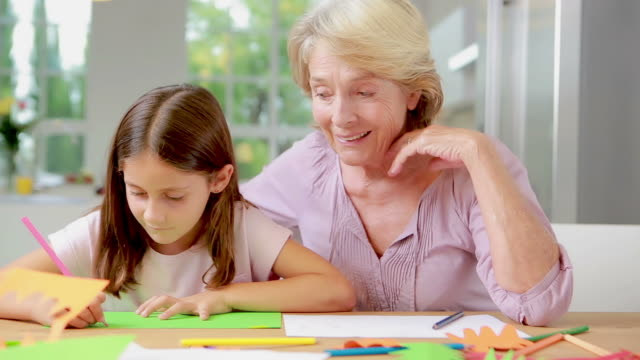 Child drawing and speaking to her grandmother