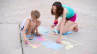 child draws a chalk on asphalt
