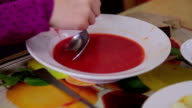 Child eating soup with a spoon