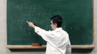Child explaining a mathematical equation on blackboard