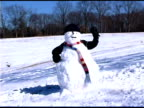 Child hiding behind snowman and waving