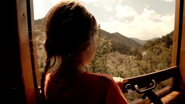 Kinder in Zug-ein kleines Mädchen, genießt Ihre erste Reise mit dem Zug. Blick auf die Berge aus dem Fenster.