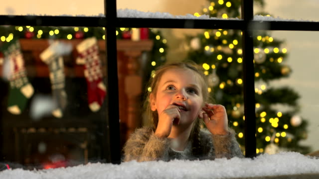 Child looking at Snow falling through window at Christmas