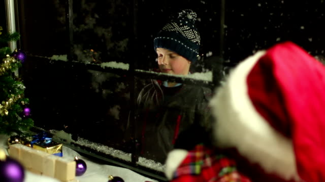 Child looking through shop window at Christmas