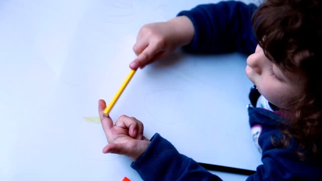 Child paints on the finger with a pencil