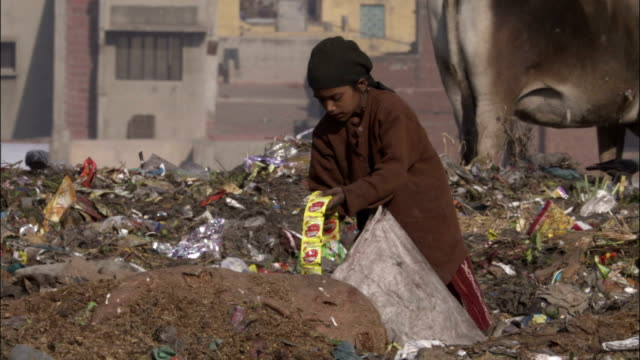 Child picks up roll of sweets and walks off in rubbish tip Available in HD.