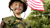 Child playing as army soldier - saluting USA flag