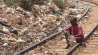 Child playing in garbage Kibera slum Nairobi Kenya Garbage Kibera slum Kenya on February 13 2011 in Nairobi Kenya