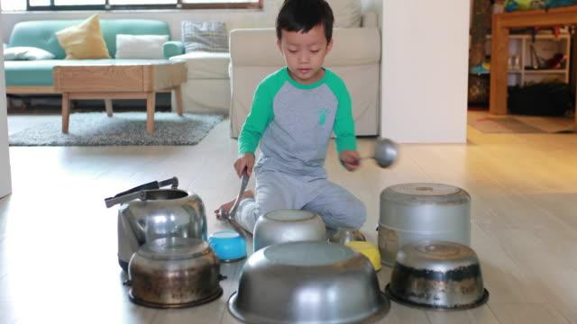 Barn som leker på golvet med kastruller och stekpannor