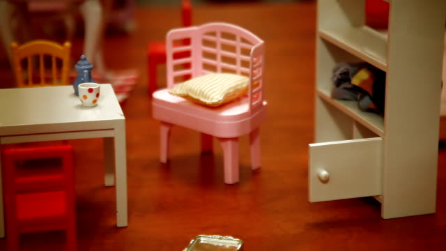Child plays with dolly furniture
