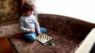 Child putting chess pieces on the chessboard