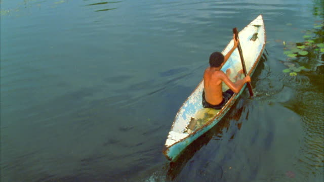 A child rows a canoe on a rural river. Available in HD.