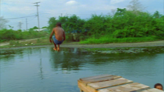 A child runs and jumps from a dock into a pond. Available in HD.