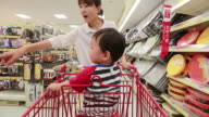 MS POV Child sitting in cart and his mother doing shopping in supermarket / Jeju, Jeju-do, South Korea