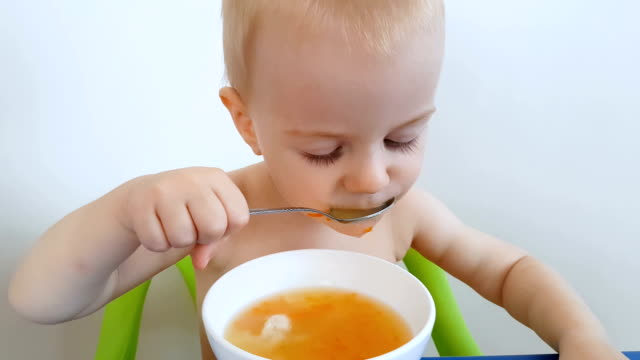 Child trying to eat alone spilling soup on himself