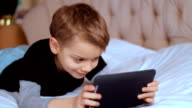 Child using digital tablet alone at home, playing game