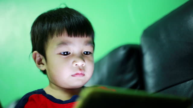 Child using digital tablet alone at home